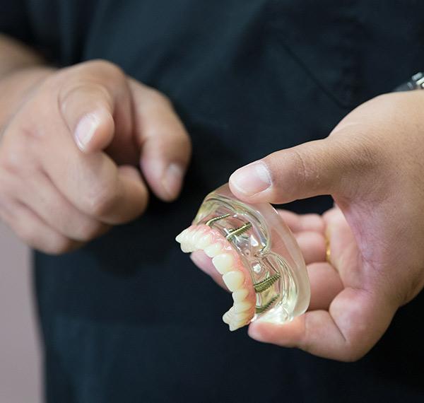 Dr. Huang shows a dental implant model - Las Vegas, NV